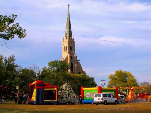 Bounce Houses And Kids Rides In Front Of The Old Church Rising Into The Sky. Image Credit: Staten Islander News Organization