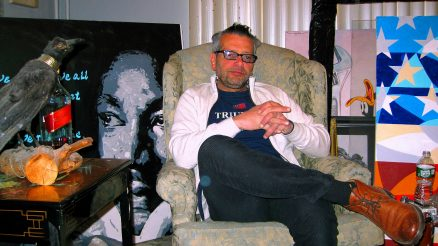 Scott LoBaido sitting in his studio, flanked by his painting of MLK on one side, and the American Flag on the other. Taken during StatenIslander.org interview on Feb.29, 2020.