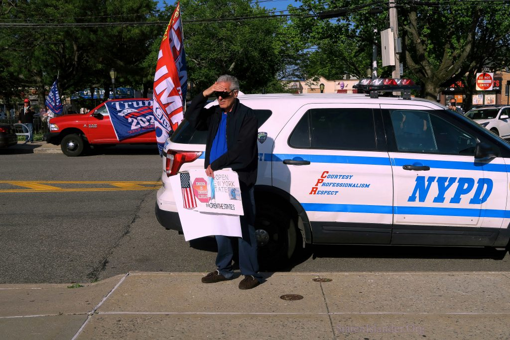 Attendee of Rally Holding Handmade Sign In Front of NYPD Vehicle