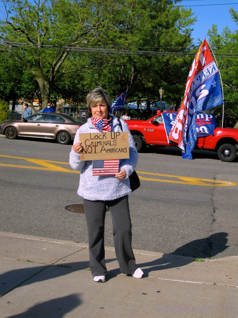 Event Particpant Holds An American Flag Photo and A Sign which Reads, 'Lock Up Criminals, Not Americans.'