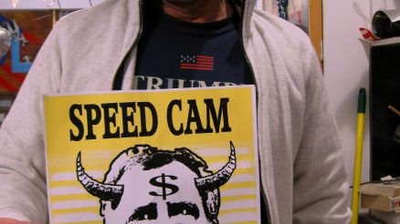 Artist Scott LoBaido Holds Up The Speed Cam Ahead Sign He Designed, Featuring Mayor DeBlasio With Horns. Photo taken at Mr. LoBaido's art studion in Grasmere.
